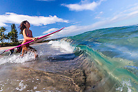 A local surfer girl runs into the ocean for a surf session, Laniakea, North Shore, O'ahu.