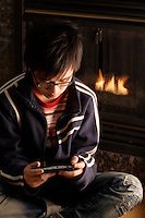 2006 Model Release Photo -<br /> 14 year old chinese teenager playing games on a handheld device SONY PS3