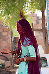 A veiled woman in a Rajasthani village is deep in conversation.