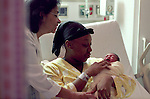 Mother resting with newborn infant with nurse in attendence