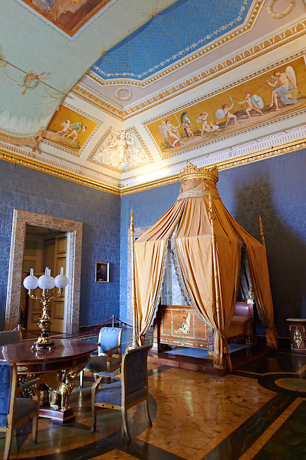"""""""The Bedroom of Francis II"""". The room furnished with a four poster bed, chest of drawers and table in the Empire Style in mahogany & gilt. The vaulted ceiling is freaked with an allegory of the victory of Napoleon over the Bourbons: the Glory of Thesus slaying the Minataur, by Giuseppe Cammarano  .  The Bourbon Kings of Naples Royal Palace of Caserta, Italy. A UNESCO World Heritage Site"""