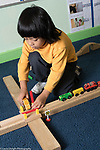 Education Preschool 4 year olds boy playing with trains and train tracks he made out of wooden blocks