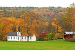 A covered bridge and country church nestled in the valleys of northeast PA showing the fall foliage on the mountain in the back.