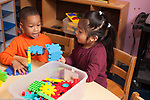 Education preschool 3-4 year olds boy and girl working together on construction made from colored plastic connecting pieces, talking, discussion