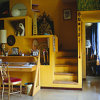 A writing desk in the yellow living room sits next to a simple staircase which leads up to the bedroom