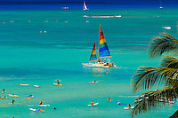 Vacationing tourist enjoy a scenic sailing cruise in a colorful boat off of world famous, palm tree lined Waikiik Beach,Oahu.