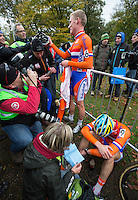03 NOV 2012 - IPSWICH, GBR - Mike Teunissen (NED) (top centre in orange) of the Netherlands talks with friends after winning the Under 23 Men's European Cyclo-Cross Championships in Chantry Park, Ipswich, Suffolk, Great Britain as his team mate silver medalist Corne van Kessel (NED) (bottom right) recovers .(PHOTO (C) 2012 NIGEL FARROW)