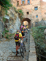Bicyclists push bikes up steep stone path in Bolsena, Ital