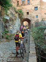 Bicyclists push bikes up steep stone path in Bolsena, Ital