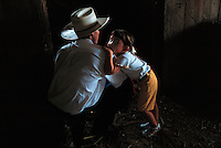 A young girl rests on her father's shoulder while he watches a a horse being shoed in the barn.