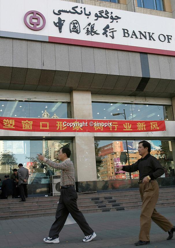 Two men walk past the Bank of China in Urumqi, Xiangjiang Uighur Autonomous Region, China.<br /> 16-SEP-04