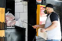 MEDELLIN - COLOMBIA, 28-04-2020: Un empleado del restaurante Akamaos desinfecta los alimentos al tiempo de recibirlos hoy en Medellín durante el día 36 de la cuarentena total en el territorio colombiano causada por la pandemia  del Coronavirus, COVID-19. / An emplye of the restaurant Akamaos desinfects the food at the time of receipt today in Medellin of during day 36 of total quarantine in Colombian territory caused by the Coronavirus pandemic, COVID-19. Photo: VizzorImage / Leon Monsalve / Cont
