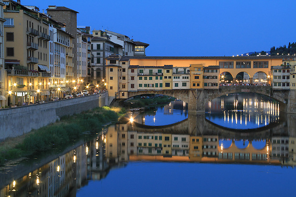 Italy, Dolomites.  <br /> About twenty minutes after the official sunset is a perfect time to shoot a cityscape at night. The sky still has color and the city lights have come on. Soon afterwards, the sky will be black.<br /> The Arno River and Ponte Vecchio, Florence, Italy.