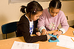 Education elementary Grade 3 science classroom two female students doing experiment on sound production and velocity horizontal
