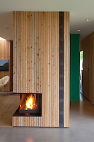 A fire burns in the grate of this contemporary minimalist fireplace in the living area