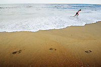 Young girl walks through surf erasing the footprints of previous visitors to the shore