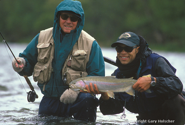 Flyfisherman & Guide, showing recently caught wild rainbow trout. Alagnak River. AK. Model Released.