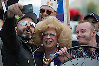 Legendary local drag queen and Mad Myrna's maintenance man Daphne DoAll LaChores has her photo taken with members of the Last Frontier Men's Club during Alaska PrideFest's Equality Parade in downtown Anchorage.