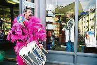 """Switzerland. Basel. Fasnacht Carnival. """"Clique""""  is a group of persons playing music in the streets during the three days of the Fasnacht Carnival. A man dressed with pink feathers takes a brake while a woman working in a chemist shop arranges various drugs. © 1997 Didier Ruef"""