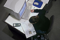 College student studying, working at computer in the library.