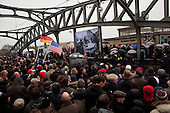 "Berlin, Germany<br /> November 9, 2009<br /> <br /> Crowds look on as Chancellor Angela Merkel and former Soviet leader Mikhail Gorbachev crossed a former fortified border, the Bornholmer bridge, on Monday to cheers of ""Gorby! Gorby!"" as a throng of grateful Germans recalled the night 20 years ago that the Berlin Wall gave way to their desire for freedom and unity.<br /> <br /> Within hours of a confused announcement on Nov. 9, 1989 that East Germany was lifting travel restrictions, hundreds of people streamed into the enclave that was West Berlin, marking a pivotal moment in the collapse of communism in Europe.<br /> <br /> Merkel, who grew up in East Germany and was one of thousands to cross that night, recalled that ""before the joy of freedom came, many people suffered.""<br /> <br /> She lauded Gorbachev, with whom she shared an umbrella amid a crush of hundreds, eager for a glimpse of the man many still consider a hero for his role in pushing reform in the Soviet Union."