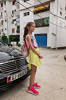 Albania. Gjirokastër. A schoolgirl with a backpack stands close to a black Mercedes parked in the town center. The buildings are dating from the communist time. Gjirokastër is a city in southern Albania. 23.05.2018 © 2018 Didier Ruef
