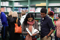 Wednesday 28 May 2014, Hay on Wye, UK<br /> Pictured: A young couple reading a book in the festival book store.<br /> Re: The Hay Festival, Hay on Wye, Powys, Wales UK.