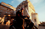 """Rome, Italy, A classic example of the """"motorini,"""" the motor scooter set of Rome: A man and woman on a motor scooter at speed near Piazza di Spagna (the Spanish Steps) at sunset."""
