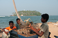 Sri Lankan boy proffers a big lobster for his friends at Beruwala fishing village, Sri Lanka