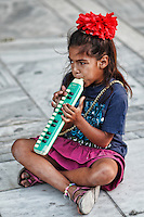 A girl playing melodica in the street of Athens, Greece