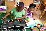 Education Preschool 3-5 year olds two girls sitting side by side looking at picture books horizontal