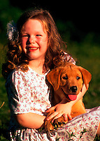 Young girl with yellow labrador retriever puppy.