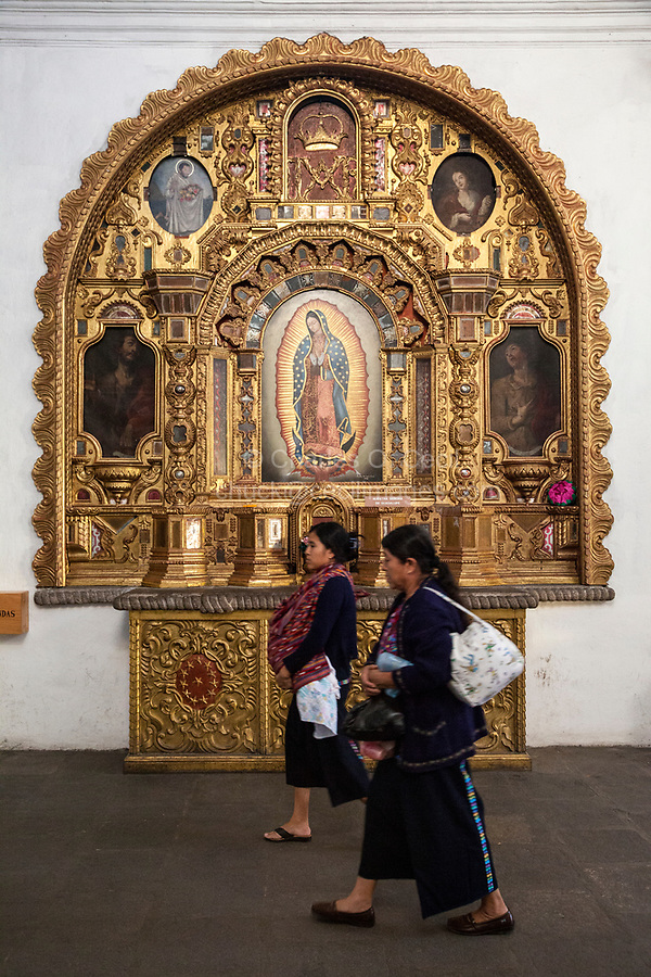 Antigua, Guatemala.  Maya Women Walk Past Shrine to Our Lady of Guadalupe, Church of San Francisco.