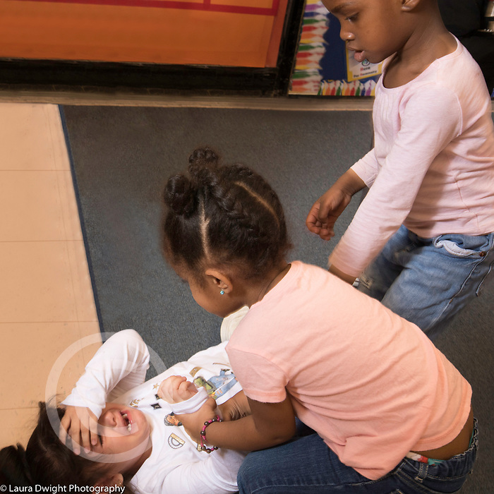 Education Preschool 3 year olds two girls moving to help fallen, crying classmate