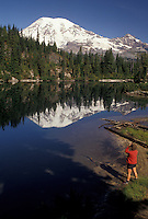 AJ3703, Mount Rainier, hiking, Mt. Rainier National Park, Cascades, Cascade Range, Washington, A woman hiker looks at the the snow covered Mt. Rainier reflecting in the calm waters of Snow Lake in the Cascade Mountain Range in Mount Rainier Nat'l Park in the state of Washington.