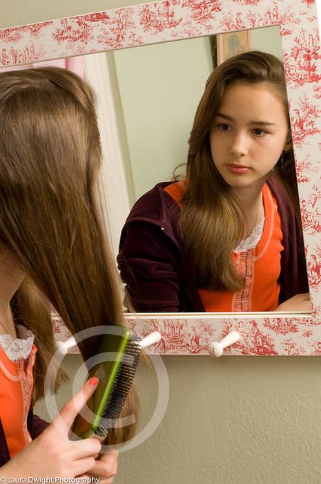 Teenage girl age 13 in bedroom looking at self in mirror self care brushing hair