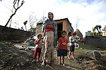 A mother stands outside her small modest house with her young children in Pokhara, Nepal.