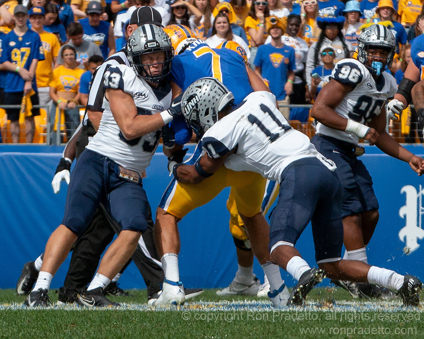 New Hampshire safeties Evan Horn (33) and Noah Stansbury (11) tackle Pitt tight end Lucas Krull. The Pitt Panthers defeated the New Hampshire Wildcats 77-7 at Heinz Field, Pittsburgh, Pennsylvania on September 25, 2021.
