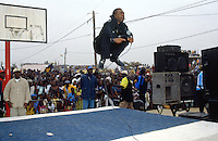 Senegal. Thiaroye sur Mer. 15 km from Dakar. Youssou Ndour. The famous worldmusic artist makes music and jumps in the air while singing for a big audience in an open air public gathering. Youssou Ndour has been invited by the population of  Thiaroye sur Mer to receive an award for his leading role in bringing african music (senegalese) to the world. He is recognised by the crowd as a true african musician and artist. © 2000 Didier Ruef
