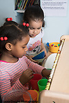 Education Preschool Childcare 2-3 year olds two girls playing together in play kitchen