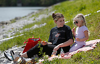 Mariah McLeod has a picnic lunch Monday, April 26, 2021, with her daughter Baylor, 4, on the side of the levee at Lake Fayetteville. Lake Fayetteville is a reservoir of Clear Creek created by Lake Fayetteville Dam in 1949. Check out nwaonline.com/210427Daily/ and nwadg.com/photos for a photo gallery.<br /> (NWA Democrat-Gazette/David Gottschalk)