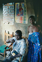 Uganda. Kayunga district. Watiyii. A man with a radio on his neck drinks a beer at home seated on a chair. His wife stands up near him by the wall where is fixed a calendar with a reprsentation of the Virgin Mary holding in her arms  her son Jesus Christ.© 2004 Didier Ruef