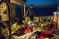 Die Sea Watch-2 Crew war am Freitag den 21. Oktober 2016 in den fruehen Morgenstunden waehrend ihrer 13. SAR-Mission vor der libyschen Kueste zu einer Position ausserhalb der 12 Meilenzone gerufen worden. Es war ein Fluechtlingsschlauchboot gesichtet worden. Als die Sea Watch-2 dort eintraf sah sie ca. 150 Menschen zusammengepfercht in einem ueberfuellten Schlauchboot sitzen. Eine Versorgung der Menschen auf dem Fluechtlingsschlauchboot mit Rettungswesten durch die Rettungs Boote der Sea Watch-2 wurde von der libyschen Kuestenwache unterbunden. Ein Soldat der Kuestenwache enterte das Schlauchboot vom Bug und machte sich dann an dem Aussenbordmotor zu schaffen. Auf dem Weg dahin schlug und trat er die Gefluechteten ein. Nach einigen Minuten entfernte sich das Boot der Kuestenwache. Dann verlor der Bug des Schlauchbootes seine Luft und es brach Panik bei den Gefluechteten aus. Sie sprangen in das Wasser und versuchten zum Schiff Sea Watch-2 zu gelangen. Die Crew warf ihnen Schwimmwesten und Rettungsringe zu, die Besatzungen der Rettungsboote der Sea Watch-2 zogen Menschen aus dem Meer, dennoch sind bis zu 30 Menschen ertrunken. Vier Ertrunkene konnten von der Sea Watch geborgen werden.<br /> Im Bild: Ein Crewmitglied spricht mit den geretten Gefluechteten an Bord der Sea Watch-2.<br /> 21.10.2016, Mediterranean Sea<br /> Copyright: Christian-Ditsch.de<br /> [Inhaltsveraendernde Manipulation des Fotos nur nach ausdruecklicher Genehmigung des Fotografen. Vereinbarungen ueber Abtretung von Persoenlichkeitsrechten/Model Release der abgebildeten Person/Personen liegen nicht vor. NO MODEL RELEASE! Nur fuer Redaktionelle Zwecke. Don't publish without copyright Christian-Ditsch.de, Veroeffentlichung nur mit Fotografennennung, sowie gegen Honorar, MwSt. und Beleg. Konto: I N G - D i B a, IBAN DE58500105175400192269, BIC INGDDEFFXXX, Kontakt: post@christian-ditsch.de<br /> Bei der Bearbeitung der Dateiinformationen darf die Urheberkennzeichnung in den EXIF- und  IPTC-Daten nich