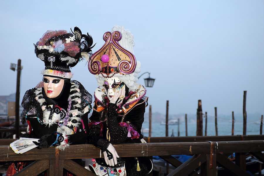 Women dressed in traditional mask and costume for Venice Carnival standing on Venice waterfront in Piazza San Marco, Venice, Veneto, Italy