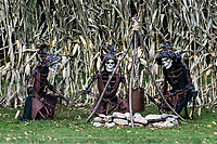 Three skeleton zombies enjoy a holloween campfire.
