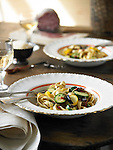 Table with two bowls of fettuccine with zucchini and crookneck squash sliced into rounds, glasses of white wine