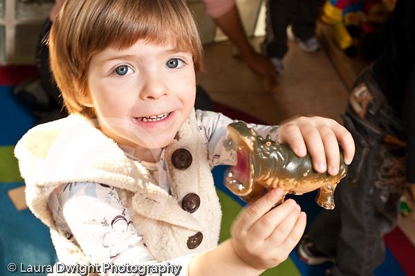 Education preschool 2-4 year olds portrait of 2 year old girl holding toy hippopotamus horizontal