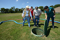 Kim Patulak (from right), human resources director for the city of Springdale, holds open a manhole Friday, Aug. 21, 2020, as Al Drinkwater, a volunteer environmental consultant; Chris Clark, financial analyst for Springdale Water Utilities; and Heath Ward, executive director of Springdale Water Utilities, look at equipment at the former Bethel Heights wastewater treatment facility. The Benton County Election Commission certified that the results of an Aug. 11 election to annex Bethel Heights into Springdale. Visit nwaonline.com/200823Daily/ for today's photo gallery.<br /> (NWA Democrat-Gazette/Andy Shupe)
