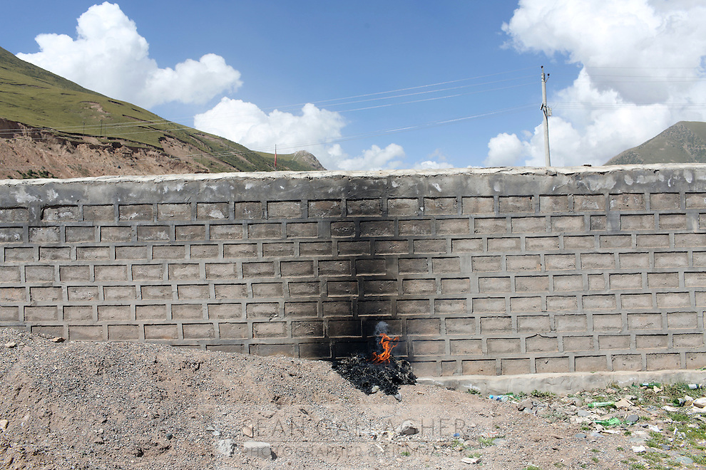 A fire burns against a wall in Zaduo, in the far interior of the Tibetan Plateau, in western China. Relocation communities been created to house nomadic herders moved from the highland grasslands. The nomads have been blamed for contributing to the deterioration of the grasslands, so have been moved, sometimes forcibly, into newly built towns that can be found across the plateau.