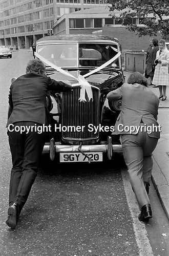 Wedding car broken down London 1970s, being pushed to get it going.   1972